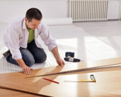 Home improvement – man laying new laminate flooring in empty room
