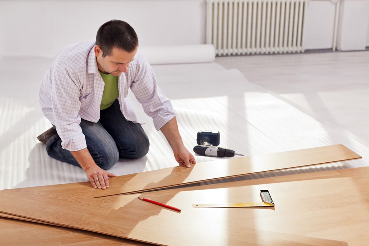 Home Improvement Man Laying New Laminate Flooring In Empty Room